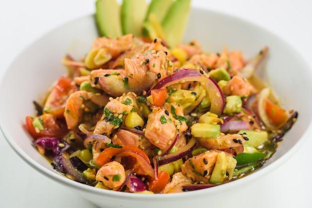 Mischen sie japanischen salat mit lachs, tomate, avocado und zwiebel.