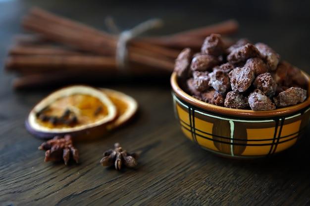 Mischen sie nüsse, trockenfrüchte und schokolade in einer keramikschale auf dem holztisch im rustikalen stil lecker und lecker...