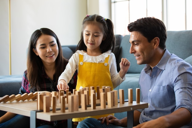 Mischen sie rassenfamilienliebhaber, kaukasischen vater und asiatische mutter mit halbbluttochter, die zusammen im wohnzimmer ein holzdominospiel mit freude und spaß spielen. idee von liebe und beziehung, süßes zuhause.