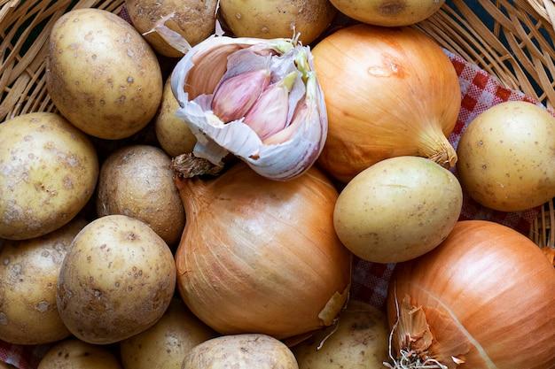 Mischen sie rohe kartoffeln, knoblauchzehen und zwiebeln in einem braunen korb