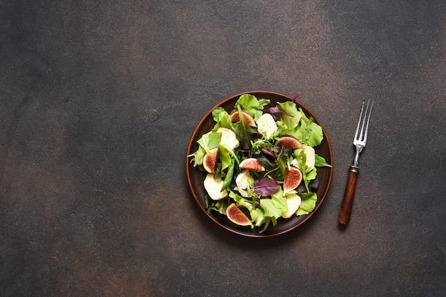 Mischen sie salat mit feigen und brie-käse auf einem betonhintergrund