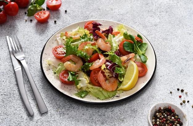 Mischen sie salat mit tomaten und gegrillten garnelen mit sauce und clematis auf dem küchentisch. konkreter lebensmittelhintergrund.