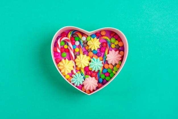 Mischen sie schokoladenbonbons liegen in der geschenkboxform des herzens auf buntem hintergrund