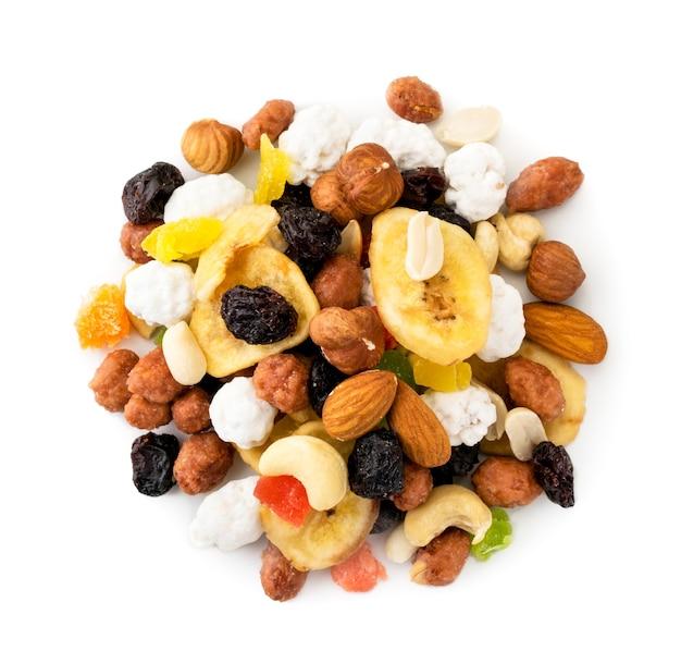 Mischen sie stapel von getrockneten früchten mit nüssen auf einem weißen hintergrund. der blick nach oben.