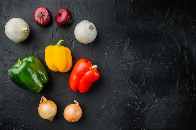 Mischen sie süße paprika und zwiebeln, auf schwarzem tisch, draufsicht flach legen