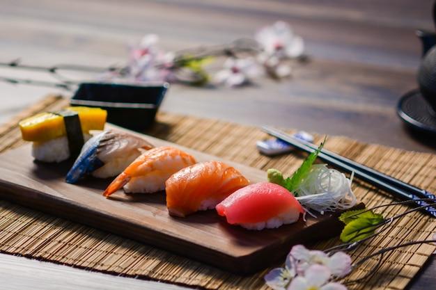 Mischen sie sushi auf holzgericht, thunfisch, lachs, wolfsbarsch, süßem ei, garnelensushi, japanischem essen