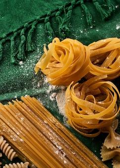 Mischen sie verschiedene nudelsorten auf grünem stoffhintergrund und kochen sie verschiedene makkaroni-konzepte