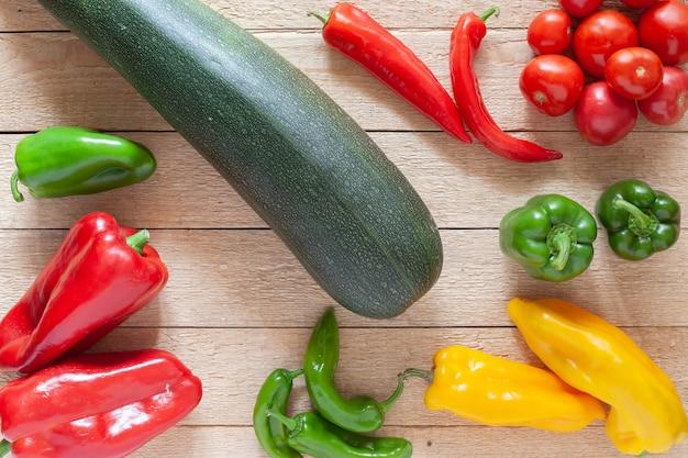Mischen sie verschiedene paprika, gurke und tomate auf holztisch