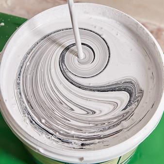 Mischen von farben im korb mit einem bohrer zum färben von wänden während der renovierung durch einen mechaniker zu hause.