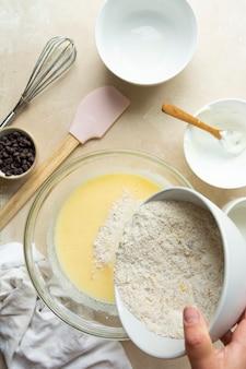 Mischen von zutaten zum kochen von kuchen oder muffins in glasschüssel, ansicht von oben. schritt für schritt rezept.