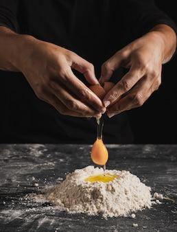 Mischendes ei der großaufnahme mit mehl für teigzusammensetzung