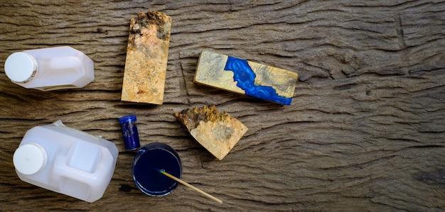Mischfarbe blaues epoxidharz in einer glasschale zum gießen von wurzelholz auf altem holztischhintergrund