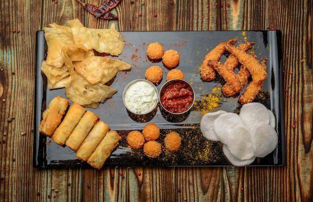 Mischimbiss mit chips, käse und garnele im teig