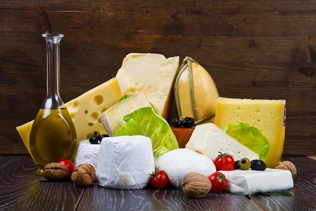 Mischkäse mit öl, olive und nuss auf hölzerner tabelle