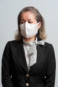Mischlingsfrau mittleren alters in formeller kleidung, die weiße chirurgische maske trägt
