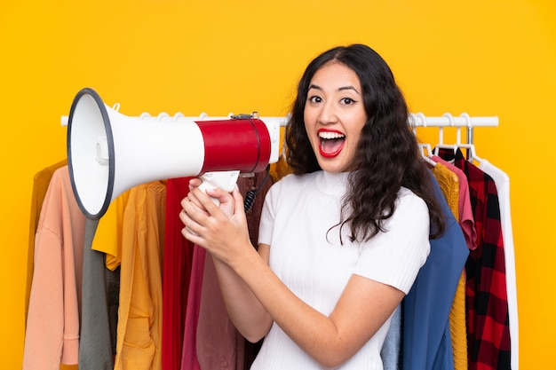 Mischrasse frau in einem bekleidungsgeschäft und in einem halten eines megaphons