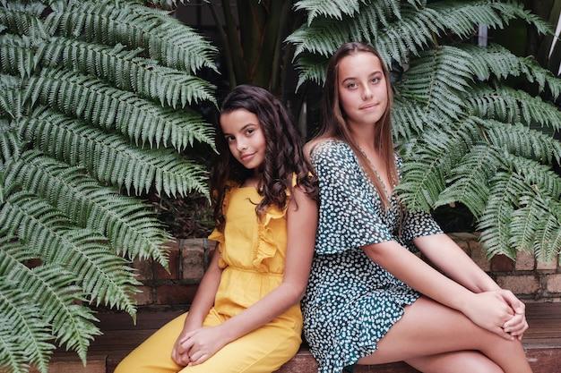 Mischrassefamilie, schöne jugendliche und jugendlich schwestern, die zusammen über grean tropischen blättern sitzen