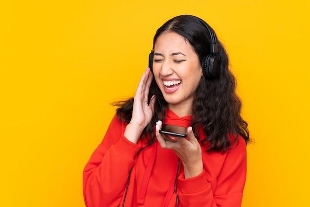 Mischrassefrau, die hörende musik eines roten sweatshirts mit einem mobile und einem gesang trägt