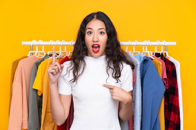 Mischrassefrau in einem bekleidungsgeschäft mit überraschungsgesichtsausdruck
