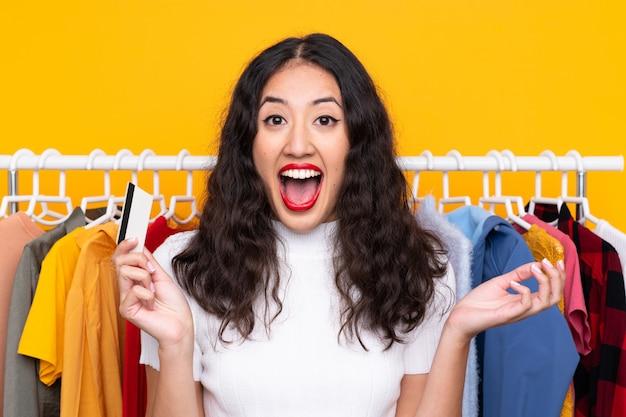 Mischrassefrau in einem bekleidungsgeschäft und in einem halten einer kreditkarte