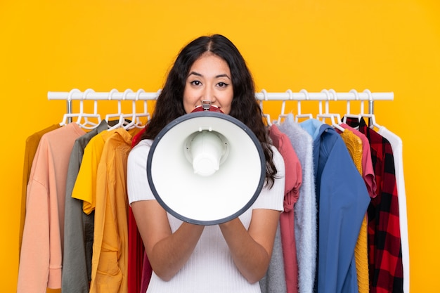 Mischrassefrau in einem bekleidungsgeschäft und in einem halten eines megaphons
