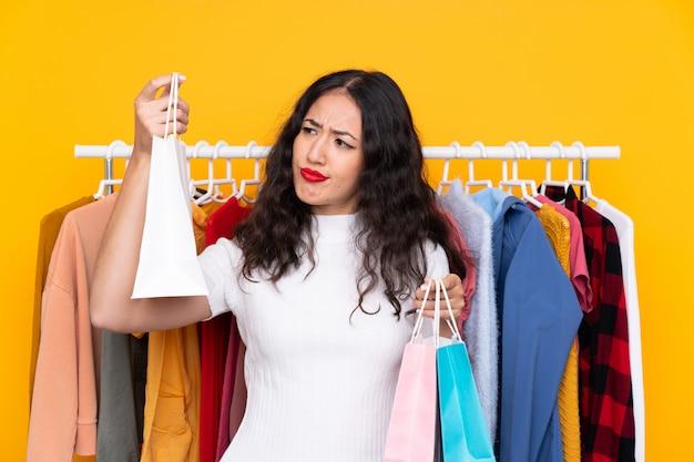 Mischrassefrau in einem bekleidungsgeschäft und mit einkaufstaschen