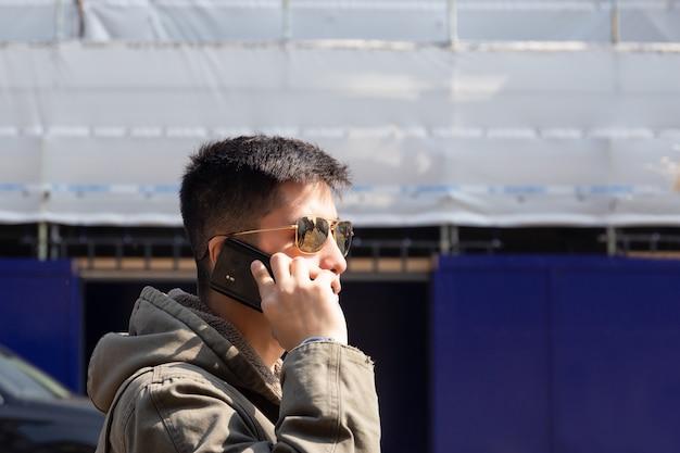 Mischrassemann mit sonnenbrille gehend auf die straße bei der unterhaltung auf mobiltelefon.