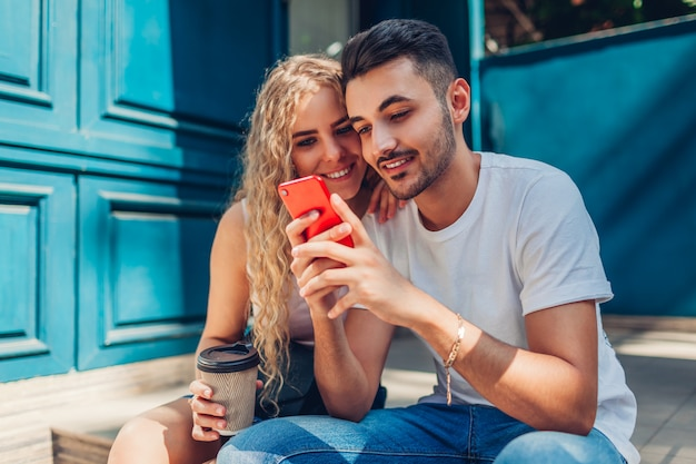 Mischrassepaare in der liebe, die in stadt geht. trinkender kaffee des arabischen mannes und der frau und anwendung des smartphone