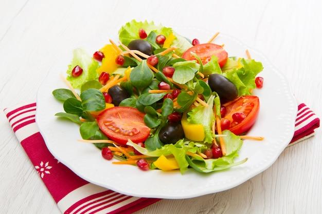 Mischsalat mit tomaten in der weißen platte auf hölzerner tabelle