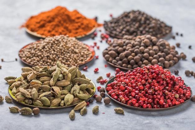 Mischung aus aromatischem koriander, schwarzem, rotem pfefferkorn, paprika in weißen bechern auf grauem betonhintergrund