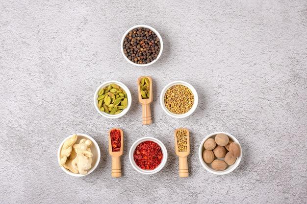 Mischung aus aromatischen gewürzen koriander, schwarzem pfeffer, bergamotte, getrocknetem ingwer, muskatnuss, paprika in weißen tassen auf grauem betontisch