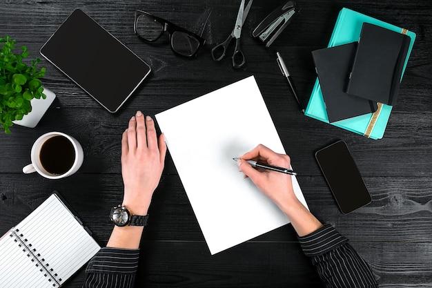 Mischung aus büromaterial und gadgets auf einem hölzernen schreibtischhintergrundansicht von oben