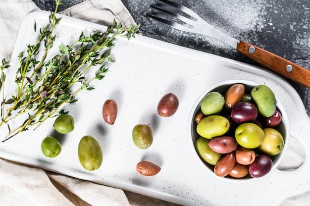 Mischung aus bunten gesalzenen oliven mit einem knochen. grauer hintergrund. ansicht von oben