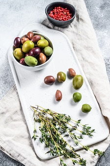 Mischung aus bunten gesalzenen oliven mit einem knochen. grauer hintergrund. draufsicht