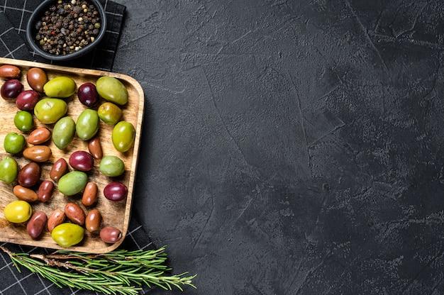 Mischung aus bunten gesalzenen oliven mit einem knochen. schwarzer hintergrund. draufsicht. platz für text