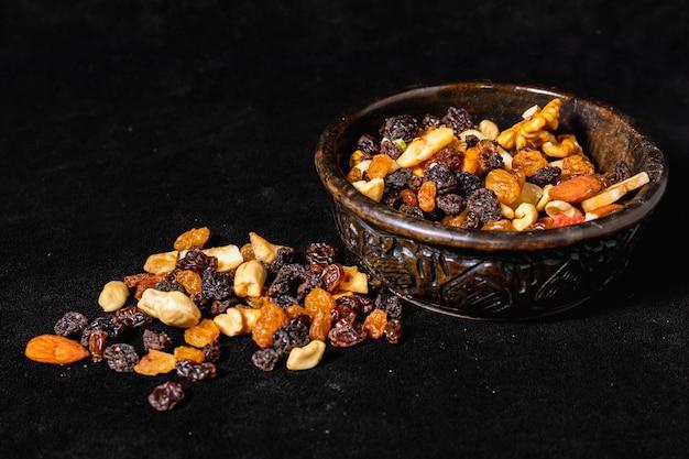 Mischung aus energetischen samen und getrockneten früchten in einer holzschale auf einer schwarzen oberfläche. 45 grad aussicht