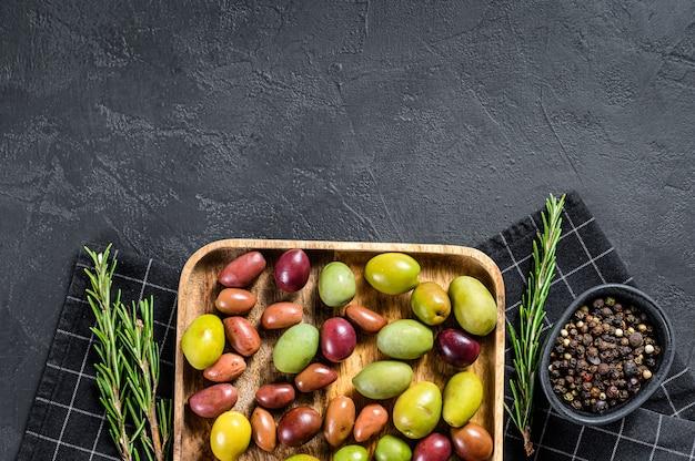 Mischung aus farbig eingelegten oliven mit einem knochen. schwarzer hintergrund. draufsicht. platz für text