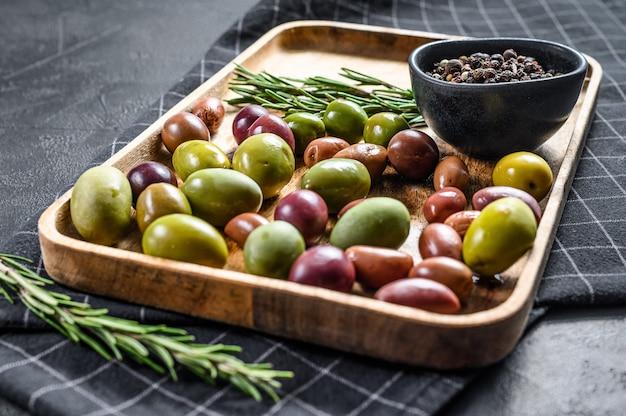 Mischung aus farbig eingelegten oliven mit einem knochen. schwarzer hintergrund. draufsicht