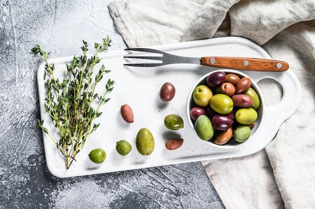 Mischung aus farbigen oliven mit einem knochen. grauer hintergrund. draufsicht