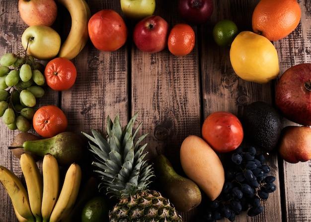 Mischung aus frischen saftigen bunten exotischen tropischen früchten auf draufsicht des hölzernen hintergrundes mit kopienraum