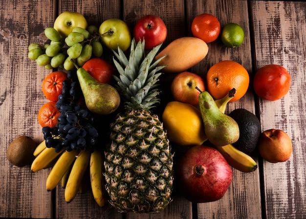 Mischung aus frischen saftigen bunten exotischen tropischen früchten auf draufsicht des hölzernen hintergrundes
