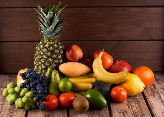 Mischung aus frischen saftigen bunten exotischen tropischen früchten auf holzuntergrund