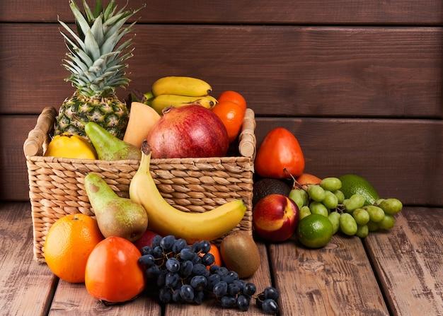Mischung aus frischen saftigen bunten exotischen tropischen früchten im korb auf holzuntergrund