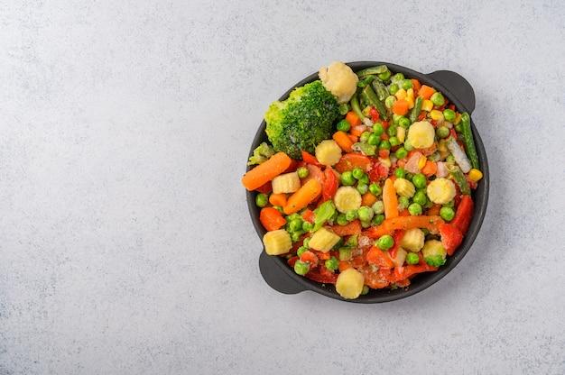 Mischung aus gefrorenem gemüse mais paprika erbsen karotten brokkoli tomaten in einer gusseisen pfanne