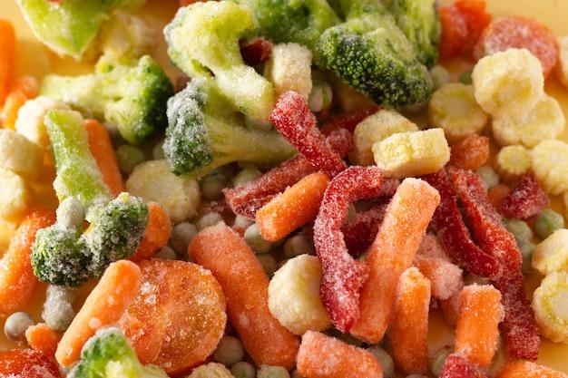Mischung aus gefrorenem gemüse: paprika, karotte, brokkoli, mini-mais, tomate und grüne erbse.