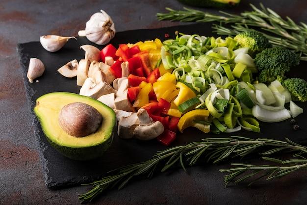 Mischung aus geschnittenem gemüse: pilze, lauch, paprika, zwiebeln, brokkoli, rosmarin, knoblauch, avocado