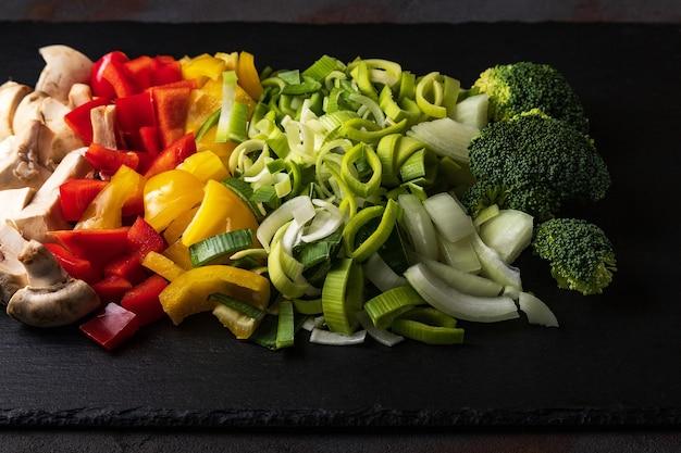 Mischung aus geschnittenem gemüse: pilze, lauch, paprika, zwiebeln, brokkoli, rosmarin, knoblauch