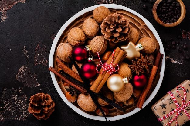 Mischung aus gesunden rohen haselnüssen und walnüssen, zimtstangen, anis, vanille, schokolade und weihnachtsspielzeug in keramikplatte auf brauner betonoberfläche