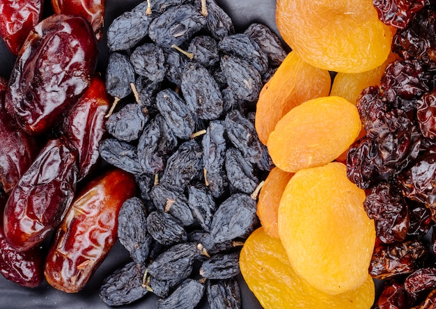 Mischung aus getrockneten früchten datiert schwarze rosinen aprikosen und kirschen auf draufsicht des schwarzen hintergrunds