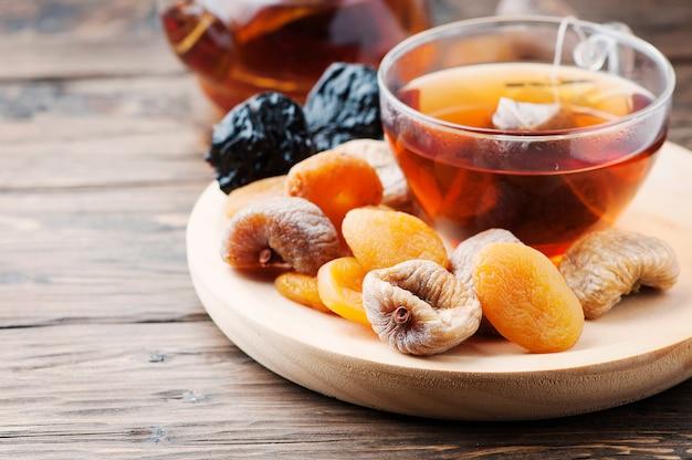 Mischung aus getrockneten früchten mit einer tasse schwarzem tee